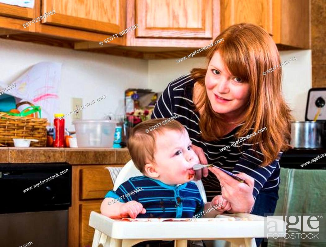 Stock Photo: Woman Feeds Baby in Kitchen.