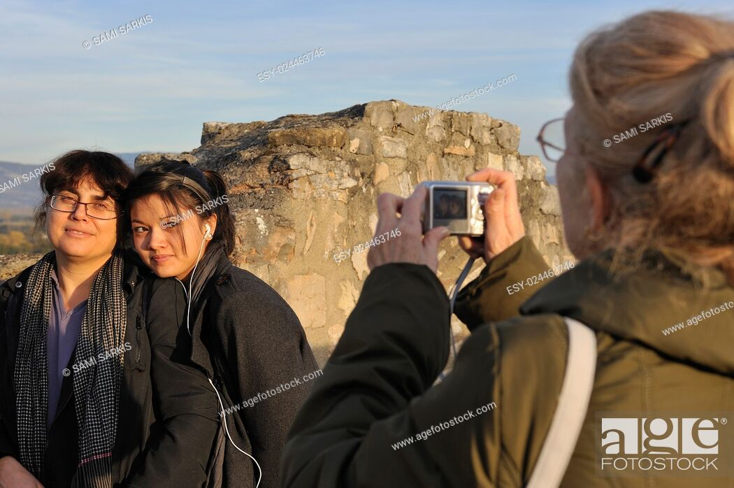 Imagen: Grandmother taking photo of her granddaughter and daughter outdoors at a tourist destination.