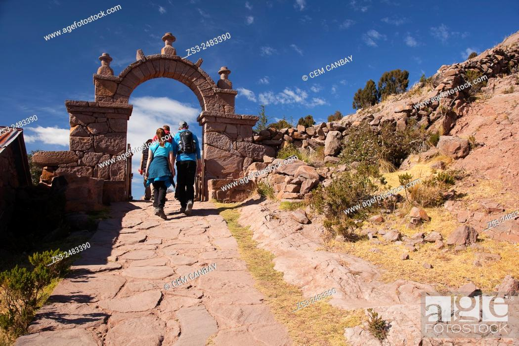 Stock Photo: Tourists walking up the stairs to reach the town center passing through a gate, Taquile Island, Titicaca Lake, Puno Region, Peru, South America.