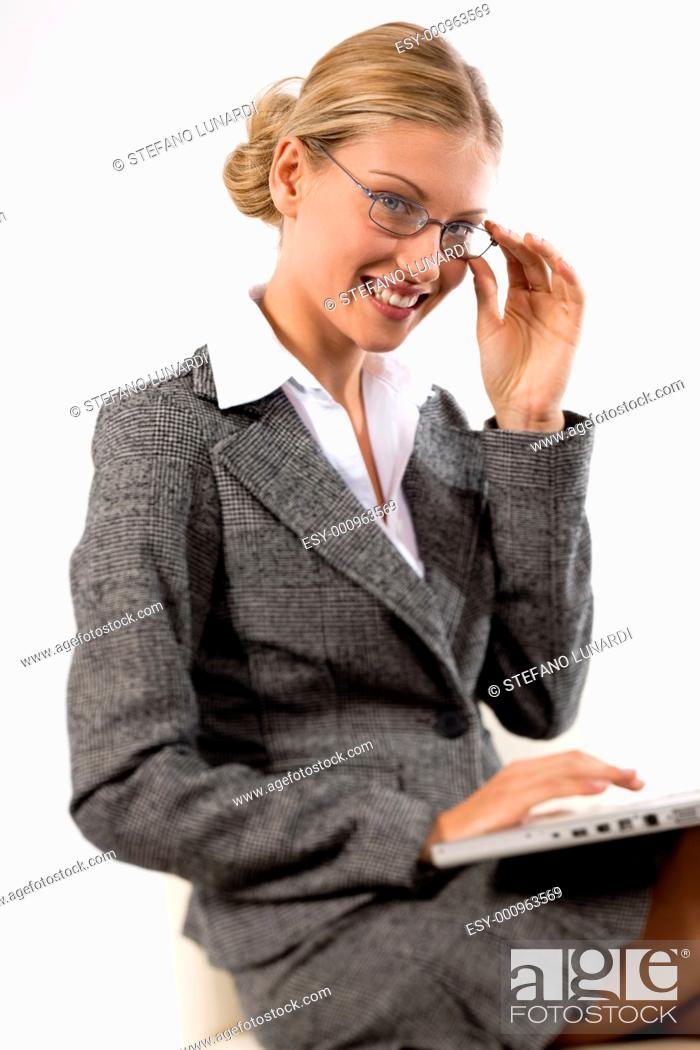 Stock Photo: Beautiful business woman working on her laptop smiling.