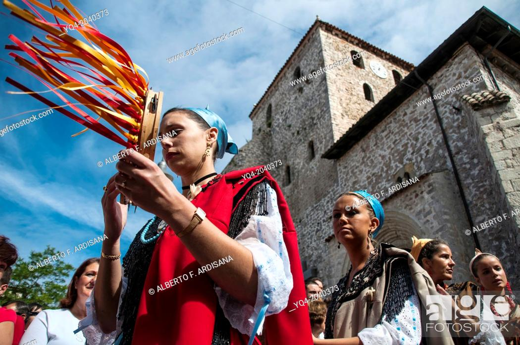 Stock Photo: Women dressed in traditional costume playing the tambourine in front of the Basilica of Llanes. Asturias.Spain.