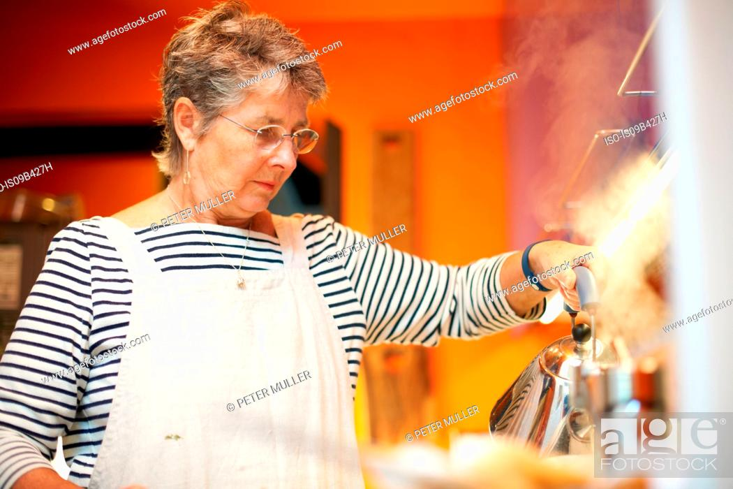 Stock Photo: Senior woman in kitchen, pouring water from kettle.