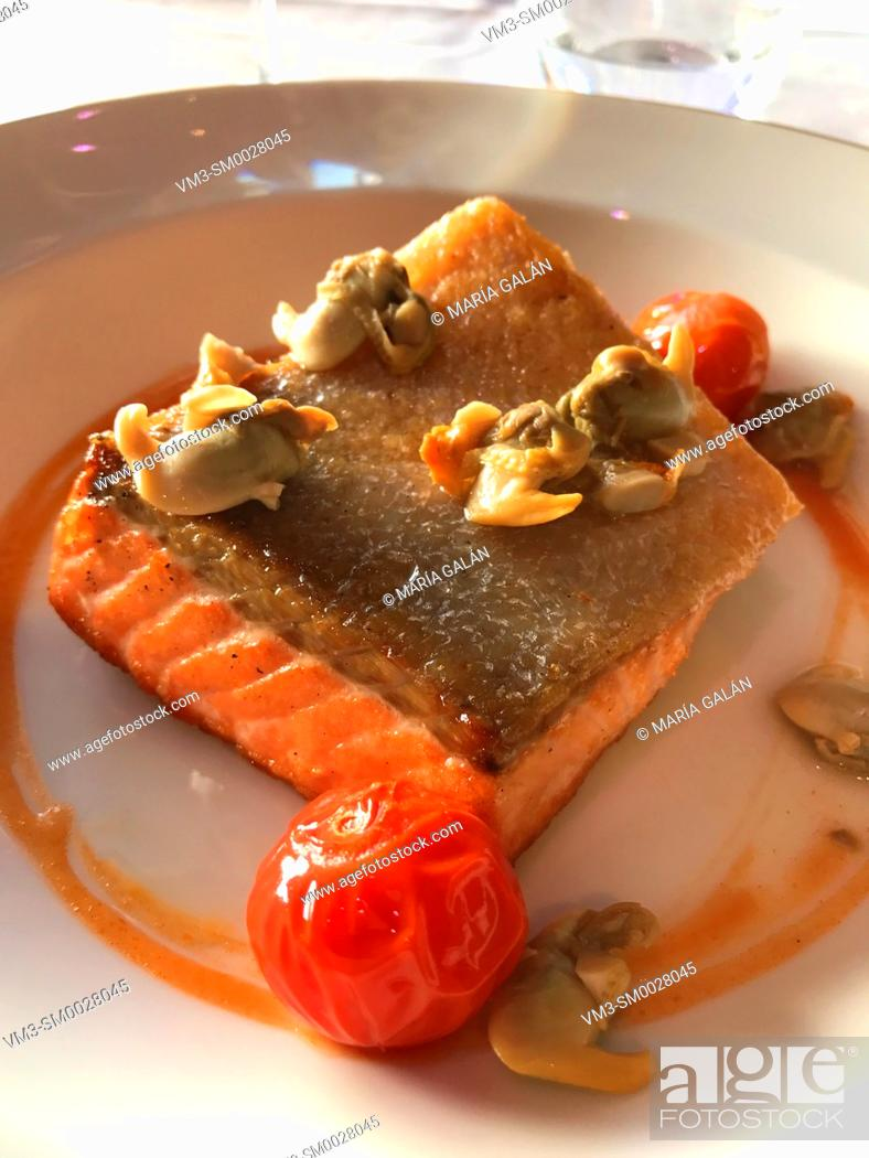 Stock Photo: Grilled salmon loin with cockles and cherry tomatoes.