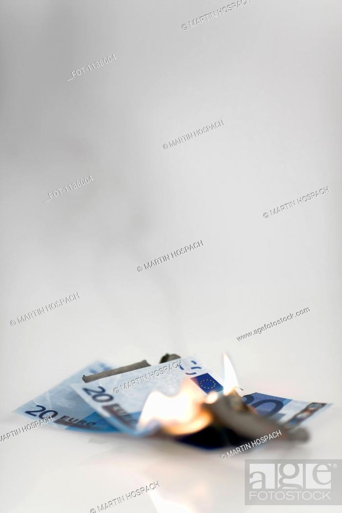 Stock Photo: Two twenty euro banknotes on fire.