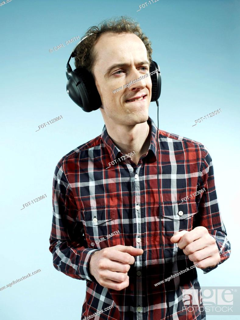 Stock Photo: A nerdy guy biting his lip and dancing while listening to headphones.
