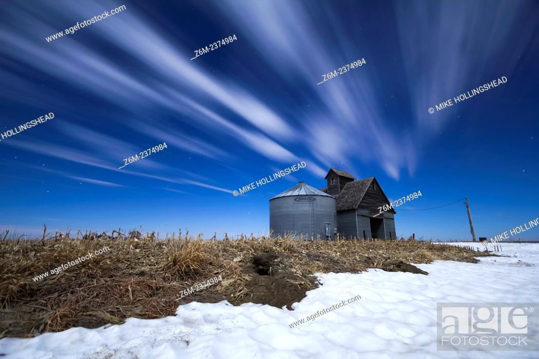 Stock Photo: Moon-lit clouds stream over a barn and silo in western Iowa.