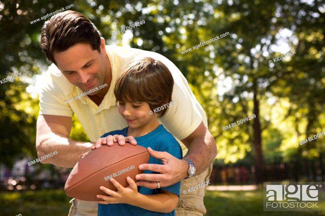 Stock Photo: Caucasian father teaching son to play football.