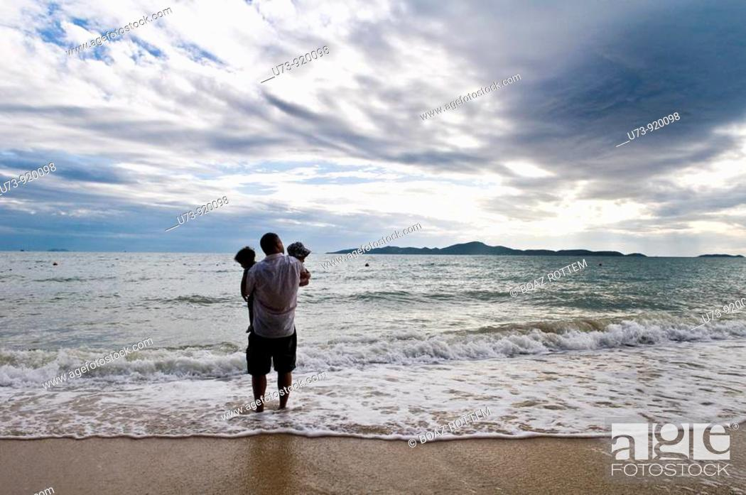 Stock Photo: Father and his twins enjoy the sunset on a tropical beach.