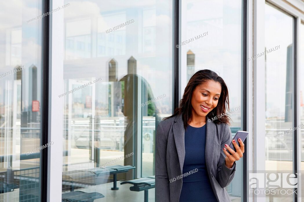Stock Photo: Businesswoman using cellphone outside ferry terminal.