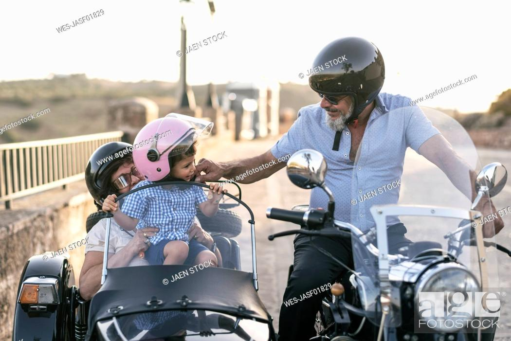 Stock Photo: Spain, Jaen, grandfather, grandmother and grandson on motorcycle with a sidecar.