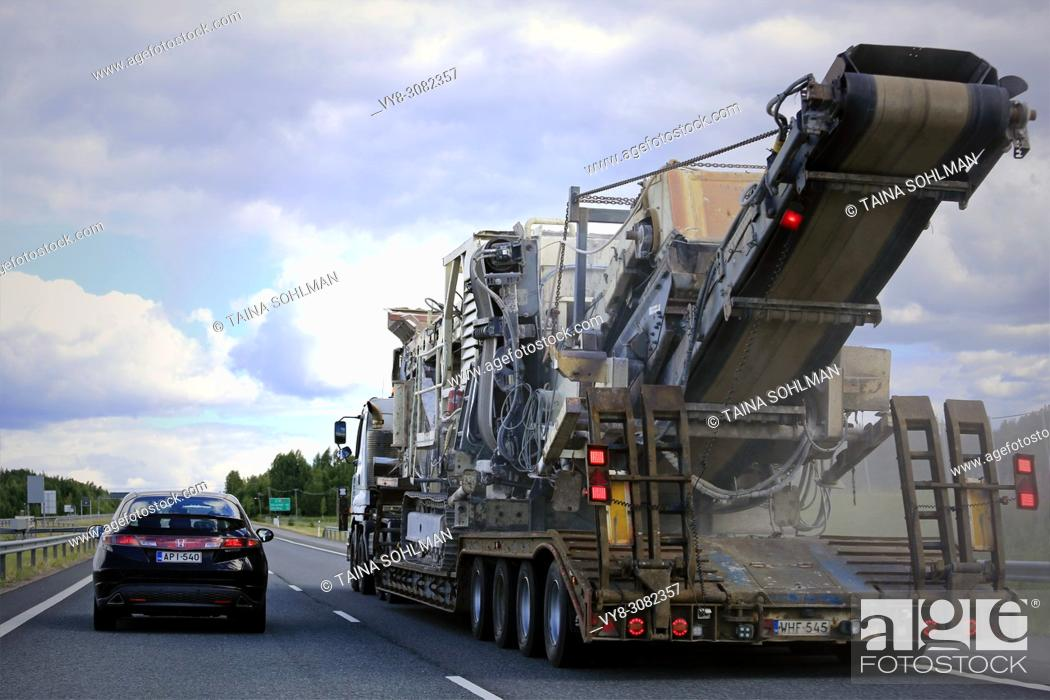 Stock Photo: Semi trailer transports large Metso crusher in motorway traffic, rear view from overtaking car, trail of dust from road. Salo, Finland - June 30, 2018.