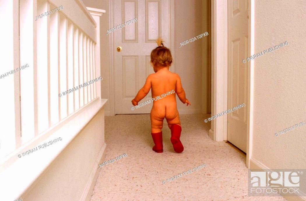 Stock Photo: little baby walking nude in corridor.