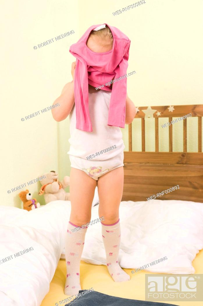 Stock Photo: Girl getting dressed on bed.
