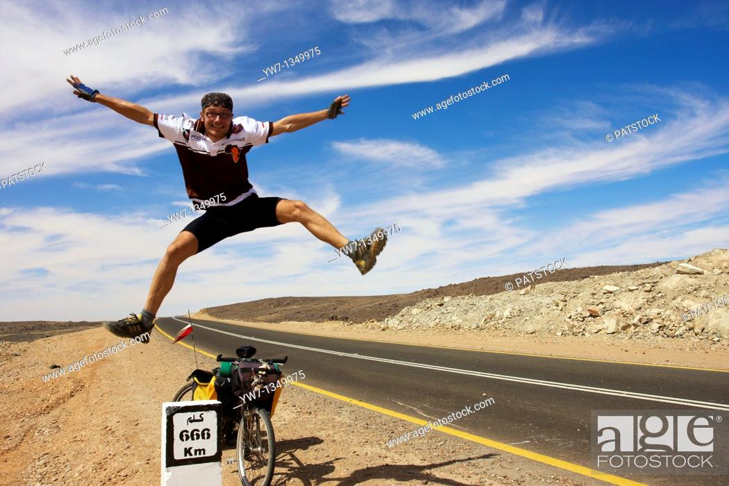 Stock Photo: Cyclist jumping by the 666 km distance bollard on the side of Sudanese road.