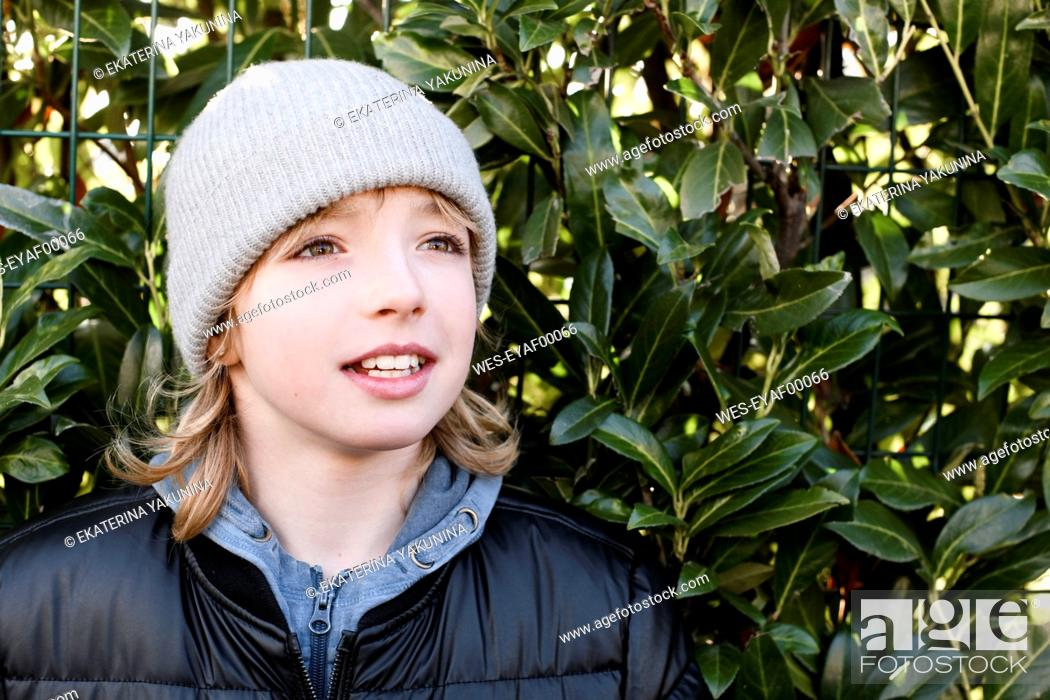 Photo de stock: Portrait of boy wearing wooly hat at a hedge.
