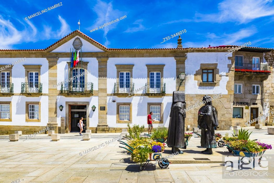 Stock Photo: Plaza Joao III, two statues made in bronze with the typical regional costumes of the region of Tras os Montes, in the background the town hall, Miranda do Douro.