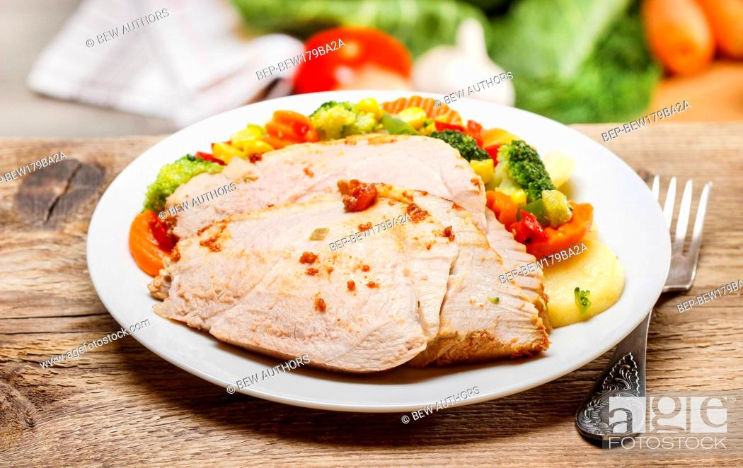 Stock Photo: Roasted meat with vegetables on wooden table. Fresh raw vegetables in the background.