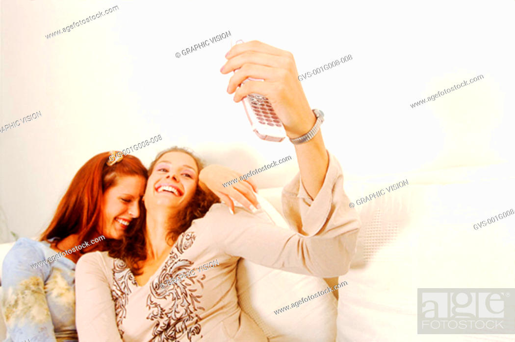Stock Photo: Two young women on a couch looking at a mobile phone.