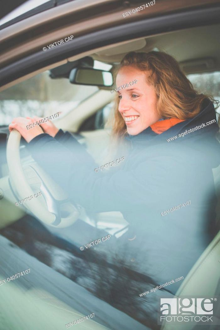 Stock Photo: Pretty young woman driving her new car.