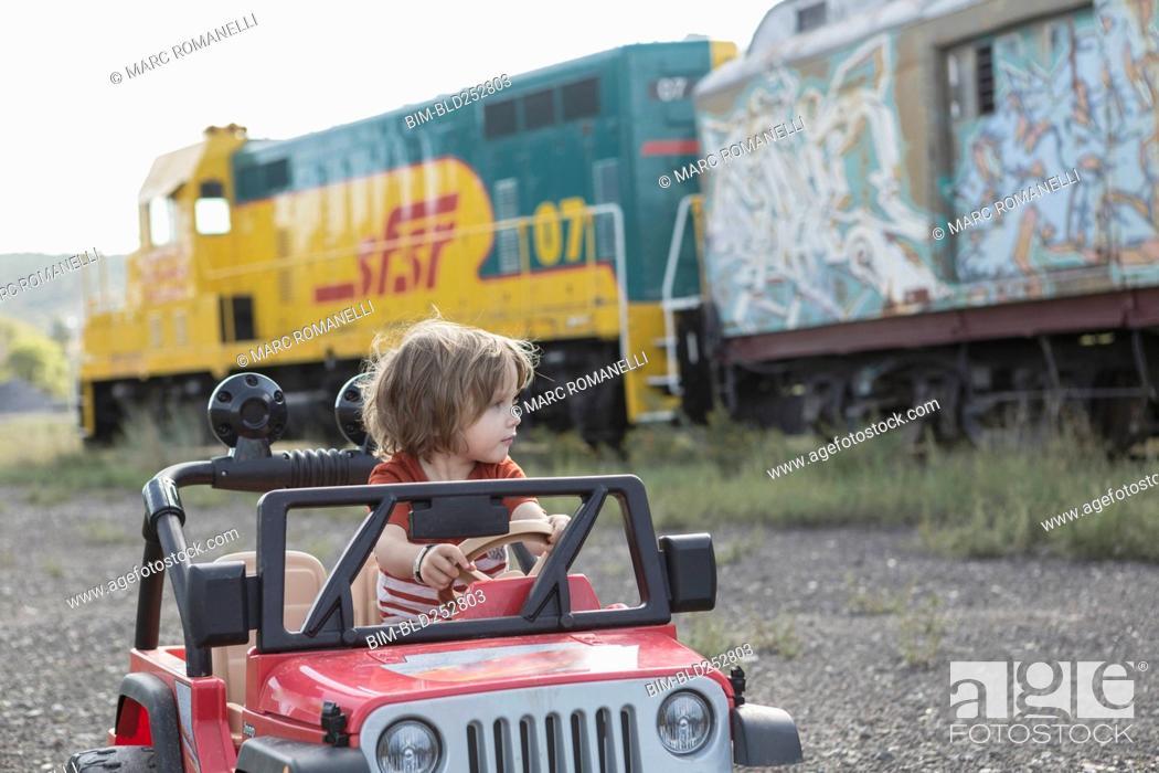Stock Photo: Caucasian boy driving toy car near train.