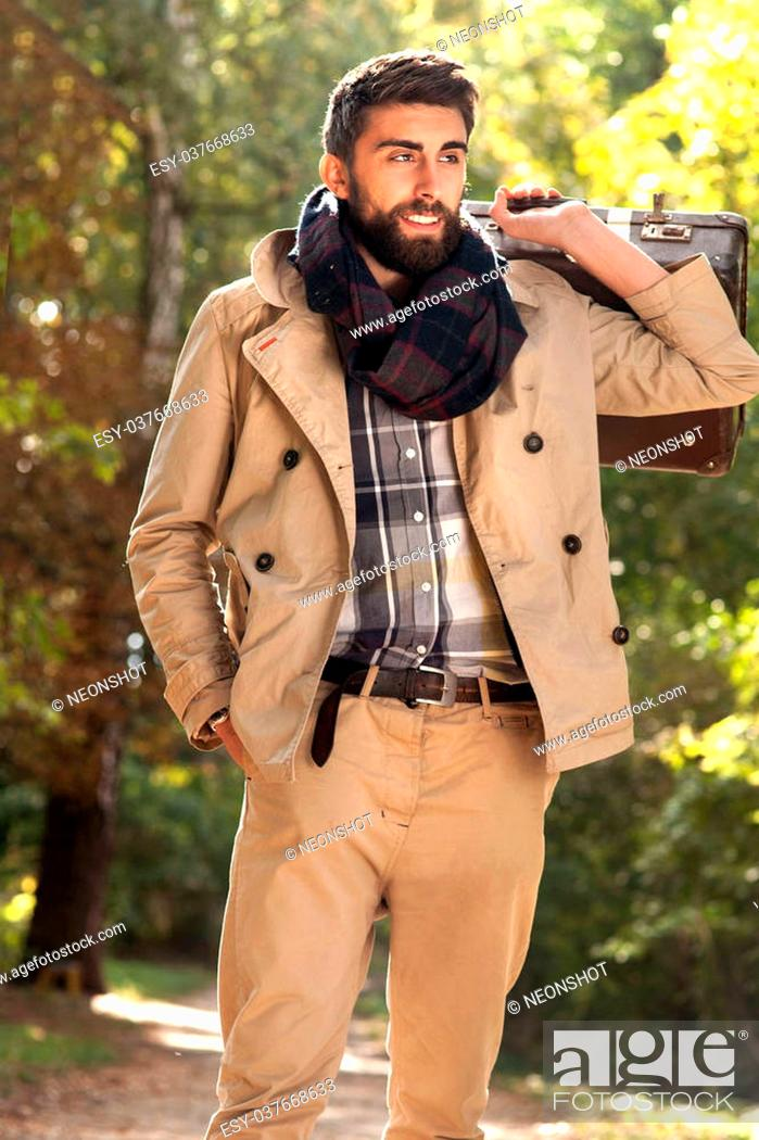 Stock Photo: Fashion photo of young handsome man with suitcases in park. Autumn. Men wearing coat and scarf. Sunny day.