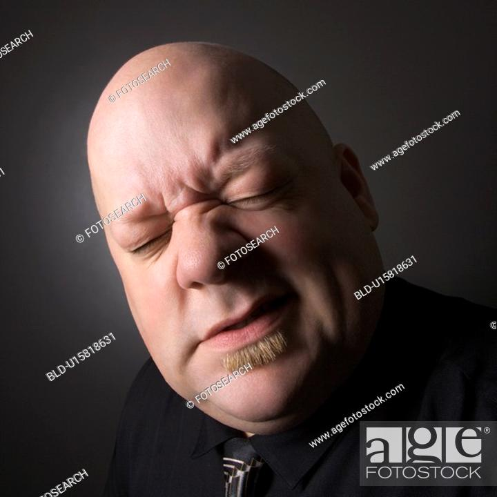 Stock Photo: Bald man squinting and making facial expression.