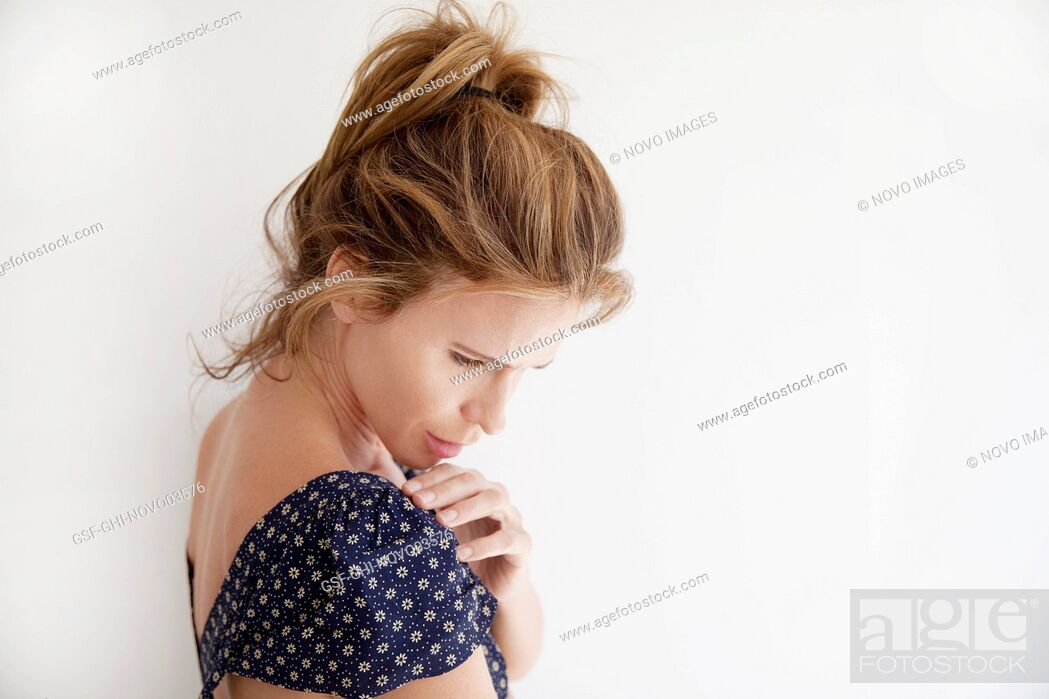Imagen: Head and Shoulders Portrait of Contemplative Mid-Adult Woman in Cap Sleeve Dress Looking Down, White Background.