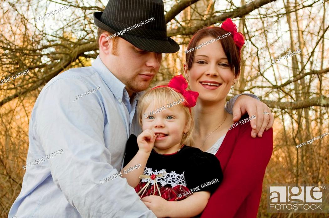 Stock Photo: This cute young family is a father embracing his wife and young daughter and they are both wearing red bows in their hair Background is intentionally blurred.