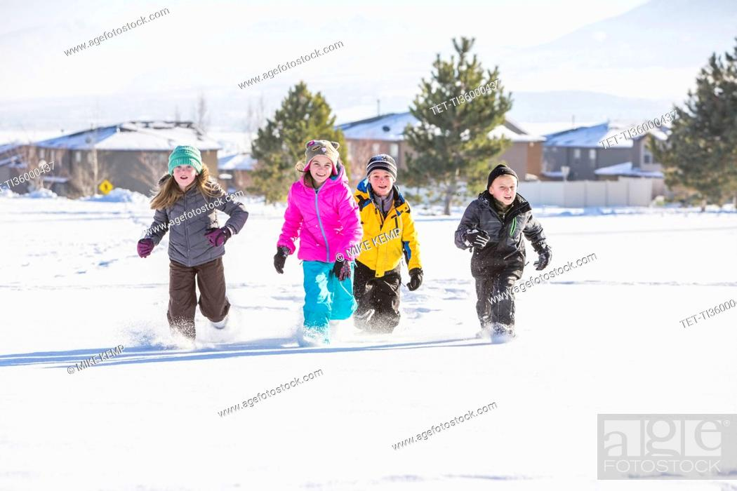 Stock Photo: Children (8-9, 10-11) running in snow.