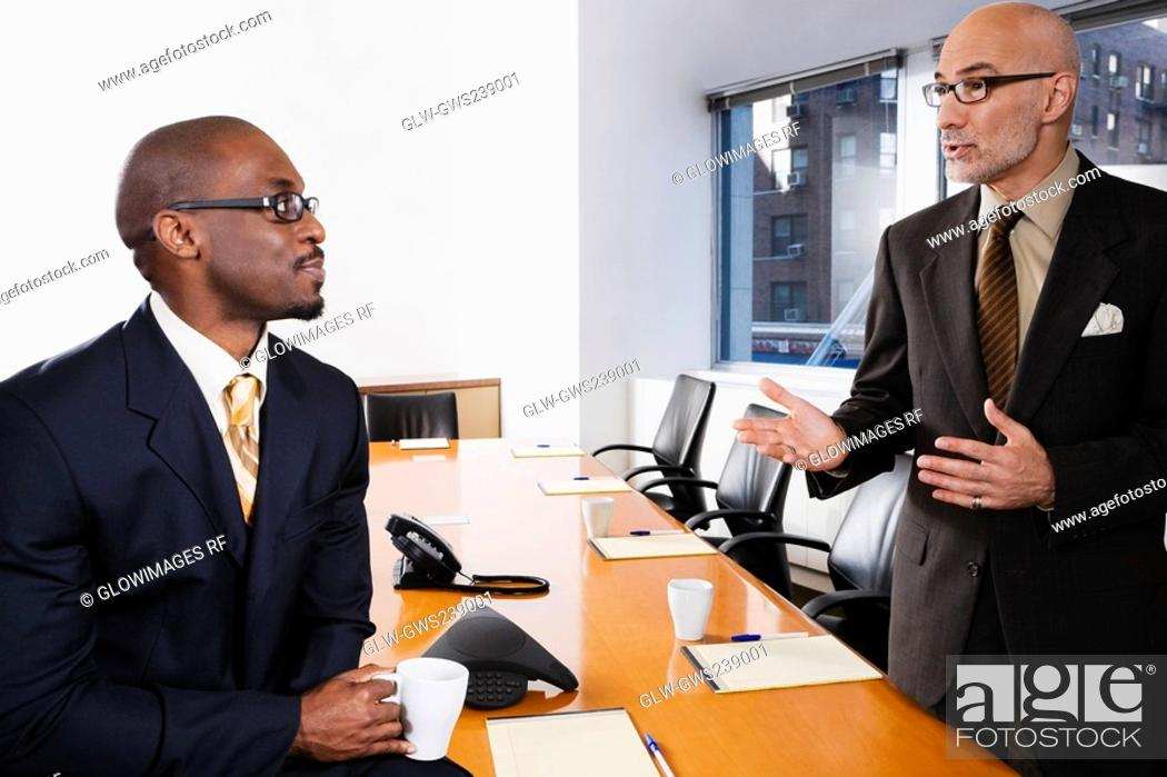 Stock Photo: Two businessmen discussing in a conference room.