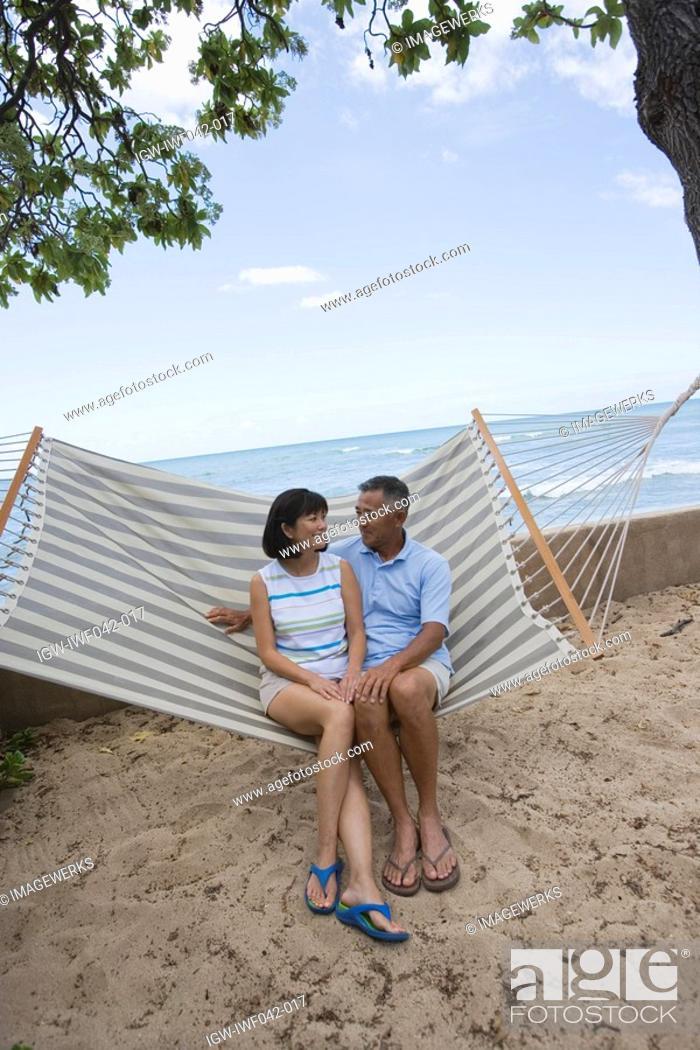 Stock Photo: A couple sitting on hammock.