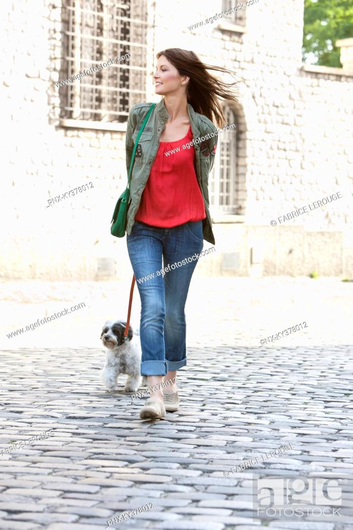 Stock Photo: Woman holding a puppy on leash, Paris, Ile-de-France, France.