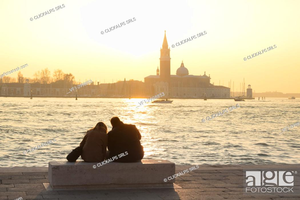 Stock Photo: Couple of tourists admire the sunset towards the island of San Giorgio maggiore from the banks of the Grand Canal, Venice, Veneto, Italy.