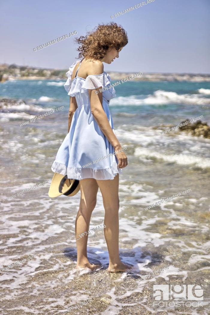 Stock Photo: woman on beach, wearing dress, sunhat, summer, in Hersonissos, Crete, Greece.