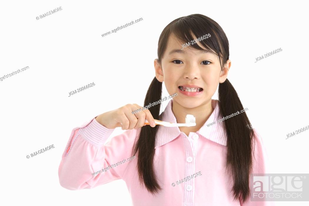 Stock Photo: Little girl holding toothbrush to brush teeth.