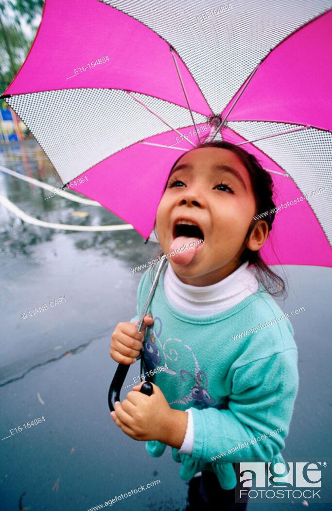 Stock Photo: Girl catching raindrops.