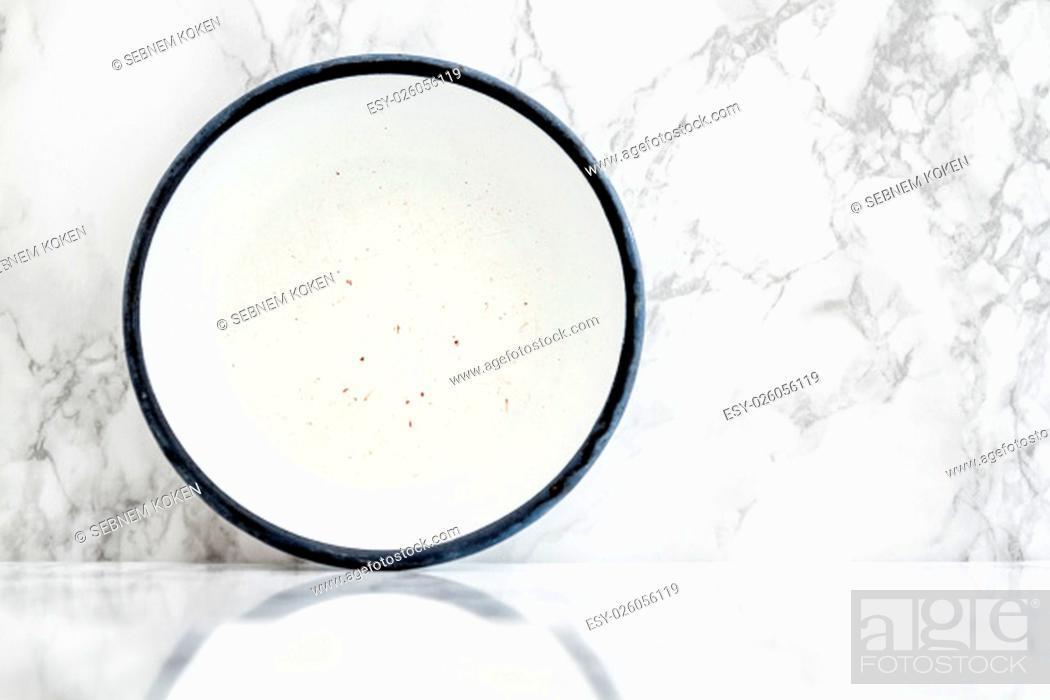 Stock Photo: Empty white vintage enamel plate on white marble background.