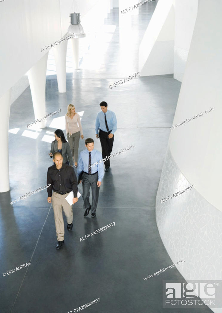 Stock Photo: Group of businesspeople walking through lobby.