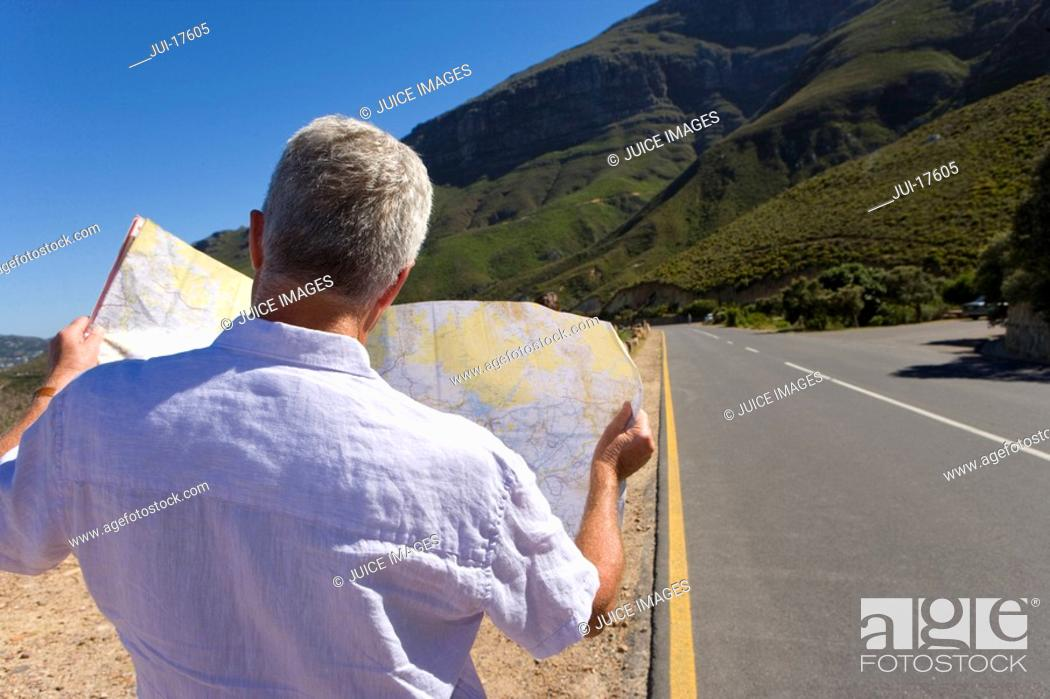 Stock Photo: Man looking at map on remote highway.