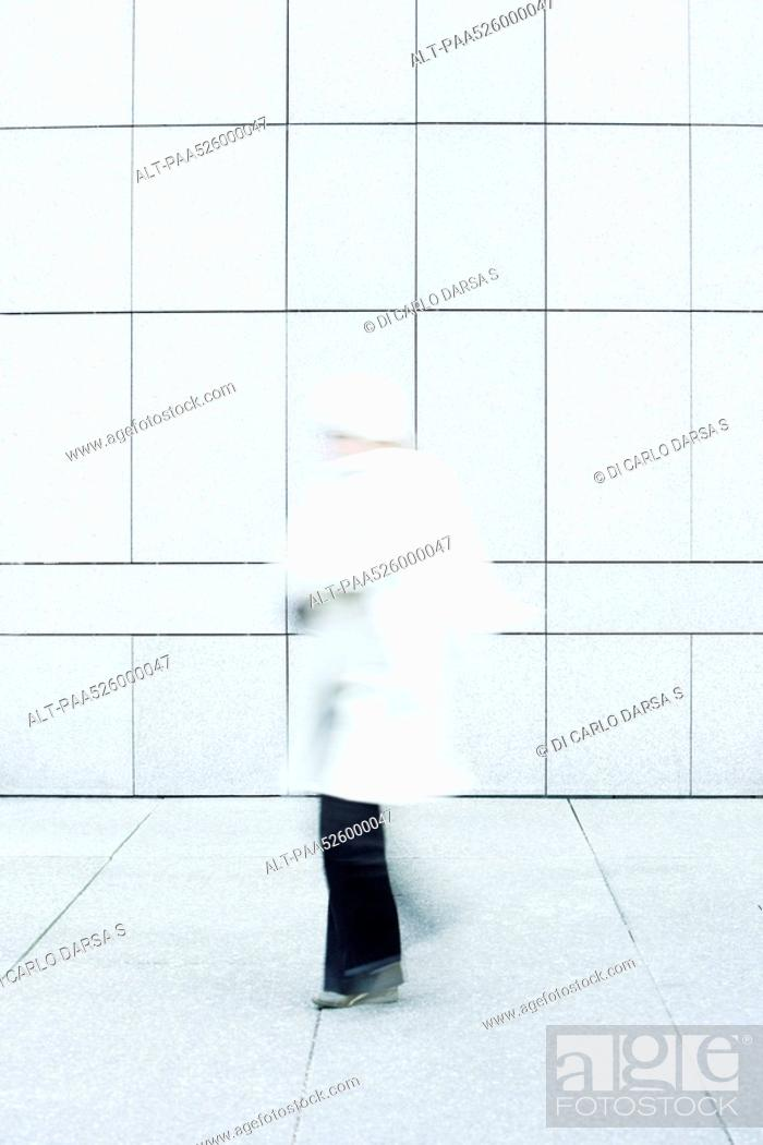 Stock Photo: Woman wearing white coat, white knit hat and white knit scarf walking down sidewalk.