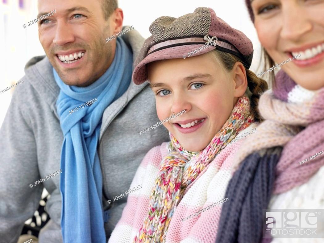 Stock Photo: Family of three sitting side by side on bench portrait close up.