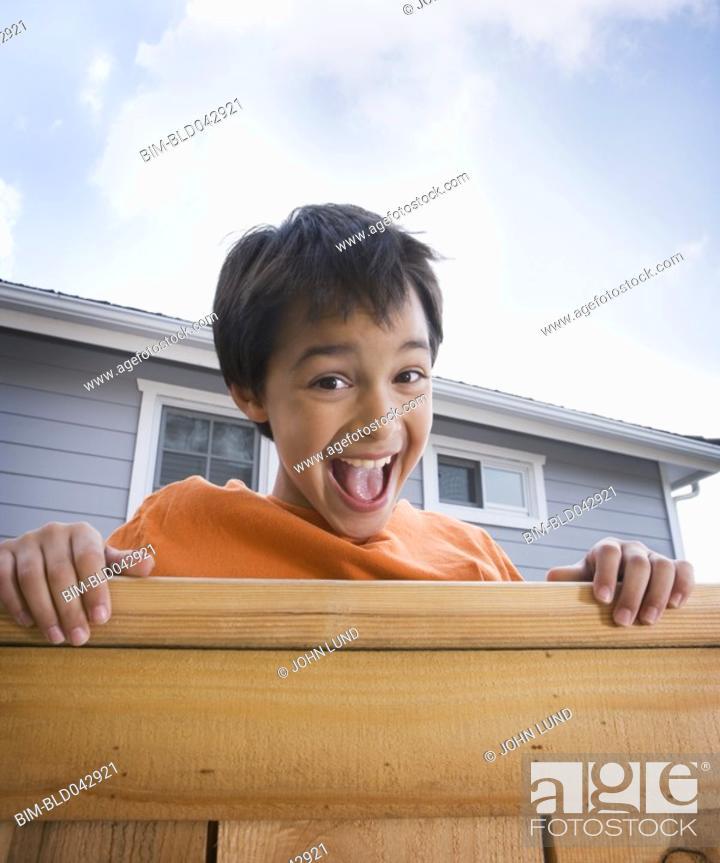 Stock Photo: Hispanic boy laughing over fence.