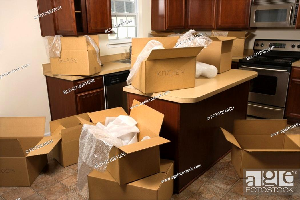 Stock Photo: Cardboard moving boxes with bubble wrap in kitchen.