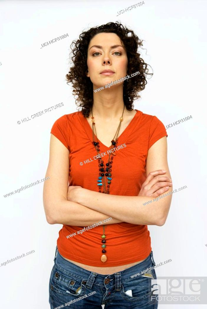 Stock Photo: Young woman standing with arms crossed.