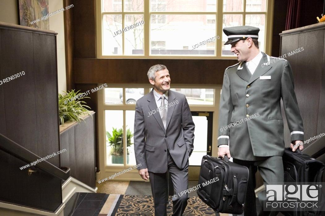 Stock Photo: Businessman and bellhop walking up stairs.