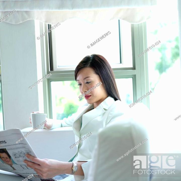 Stock Photo: Businesswoman reading a newspaper.