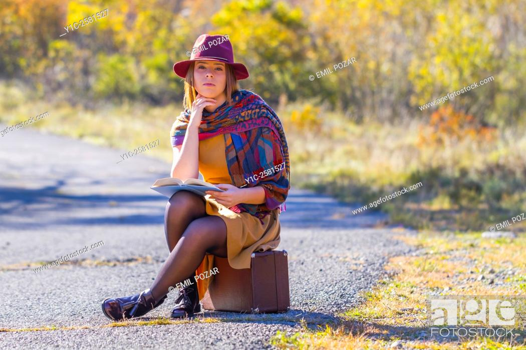 Stock Photo: Young woman dressed old-fashioned is waiting for transport.