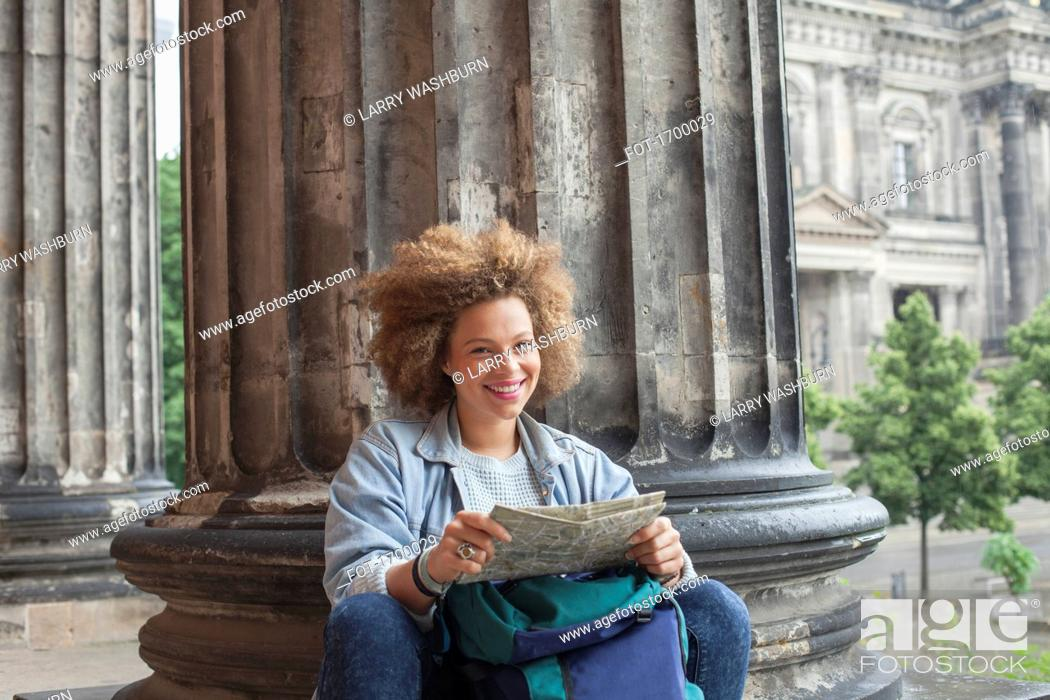 Imagen: Portrait of smiling young Afro female tourist sitting with map against column at Altes Museum.