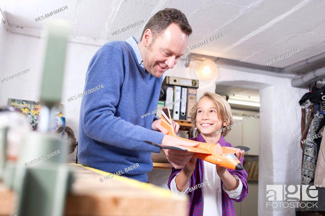 Stock Photo: Germany, Leipzig, Father and son repairing toy plane.