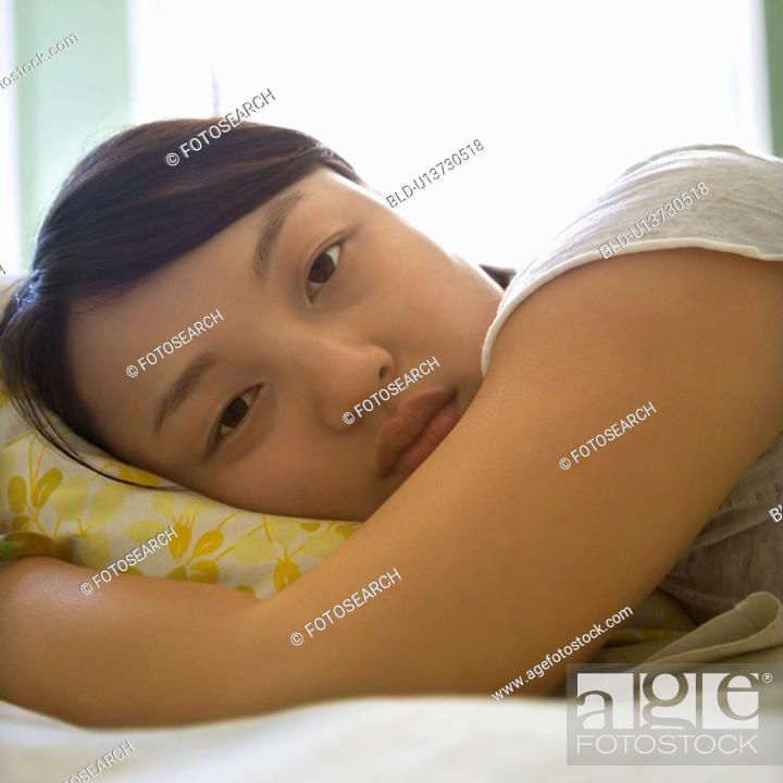 Stock Photo: Woman lying in bed with head on pillow.